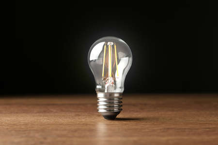Glowing light bulb for modern lamps on table against black background