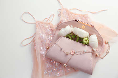 Flat lay composition with stylish clutch bag and spring flowers on light background