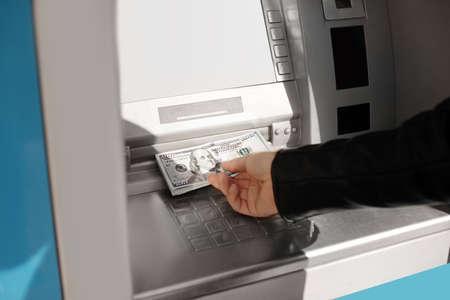 Hombre tomando dinero del cajero automático al aire libre, vista de cerca