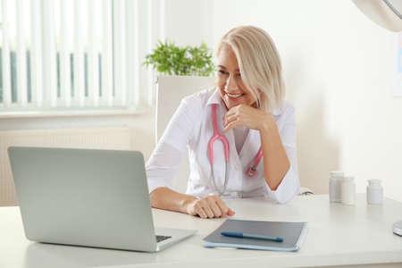 Médico consulta paciente mediante chat de video en la computadora portátil en la clínica