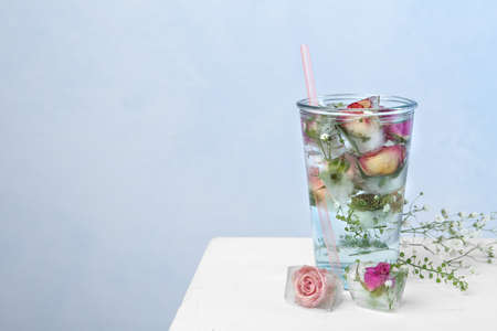 Glass of water with ice cubes and flowers on table against color background, space for text