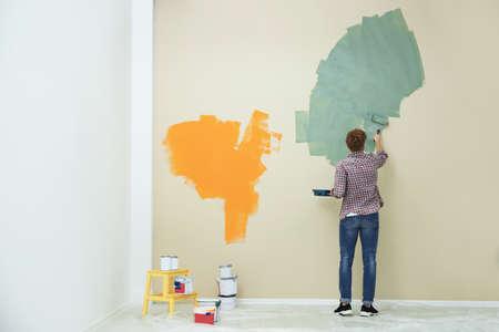 Junger Mann Malerei Wand drinnen, Platz für Text. Reparatur zu Hause Standard-Bild
