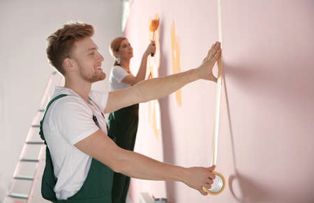 Professional decorators painting wall indoors. Home repair service 스톡 콘텐츠