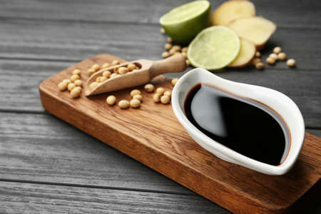 Board with dish of soy sauce and beans on table