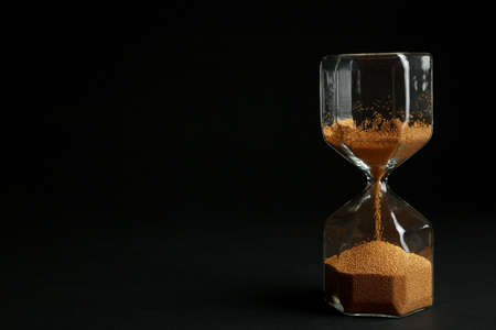 Hourglass with golden sand on black background. Space for text