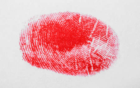 Red fingerprint on white background. Friction ridge pattern