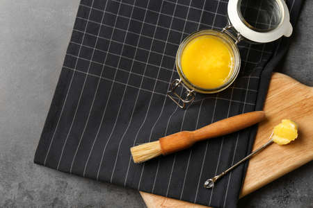 Flat lay composition with clarified butter and basting brush on grey background. Space for text