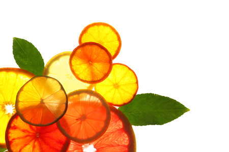 Illuminated slices of citrus fruits and leaves on white background, top view