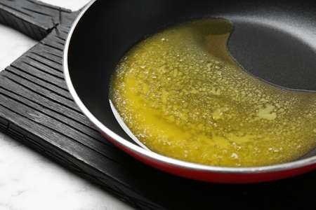 Frying pan with melting butter on table, closeup