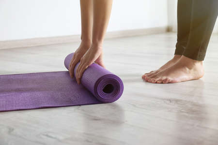 Woman rolling yoga mat on floor indoors, closeup