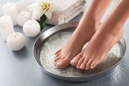 Closeup view of woman soaking her feet in dish with water on grey floor. Spa treatment