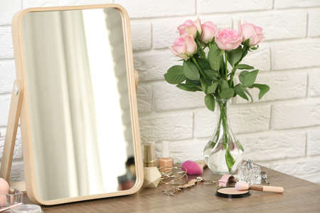 Different makeup products and accessories on dressing table in room interior Stock Photo