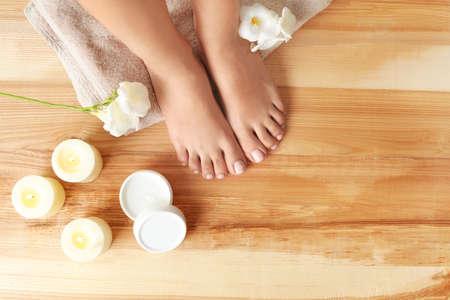 Vista superior de la mujer con hermosos pies, velas, flores y crema hidratante sobre piso de madera, espacio para texto. tratamiento de spa