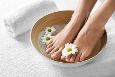 Closeup view of woman soaking her feet in dish with water and flowers on white towel, space for text. Spa treatment Banque d'images
