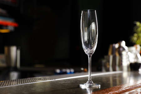 Empty clean champagne glass on counter in bar. Space for text
