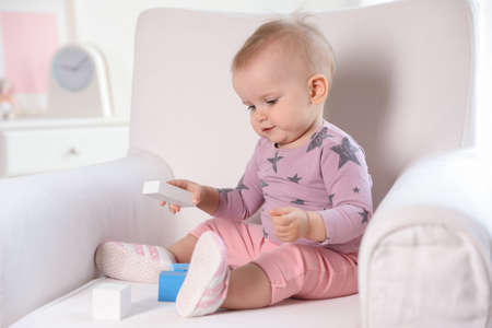 Cute baby girl playing with building blocks in armchair at home 版權商用圖片