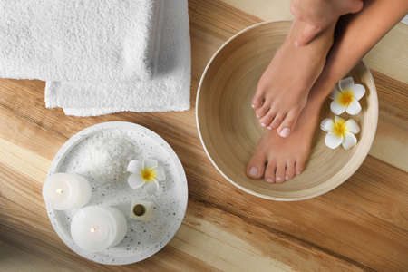 Woman soaking her feet in dish with water and flowers on wooden floor, top view. Spa treatment