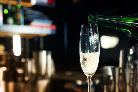 Pouring champagne from bottle into glass in bar. Space for text
