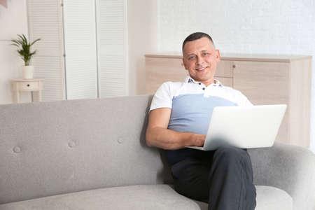 Reifer Mann mit Laptop, der zu Hause auf dem Sofa sitzt Standard-Bild