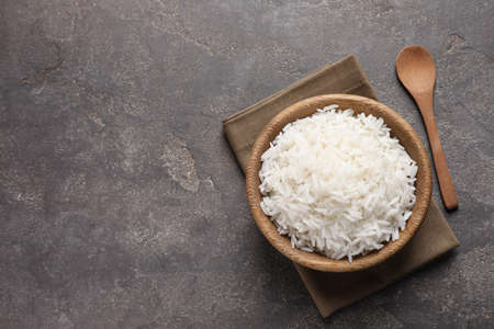 Bowl of delicious cooked rice served on table, flat lay. Space for text Reklamní fotografie