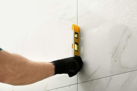 Man die de juiste installatie van keramische tegels controleert met niveau op de muur, close-up. Bouw- en renovatiewerken