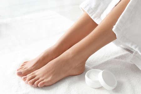 Mujer con hermosos pies y crema hidratante en toalla blanca, primer plano. tratamiento de spa