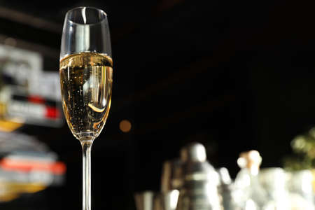 Glass of champagne in bar, low angle view. Space for text