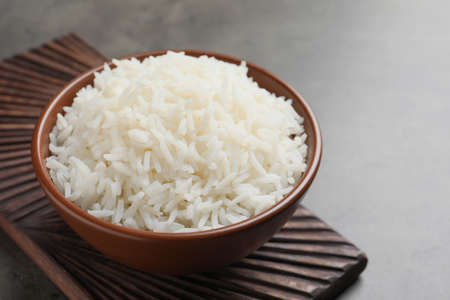 Bowl of tasty cooked white rice on grey table