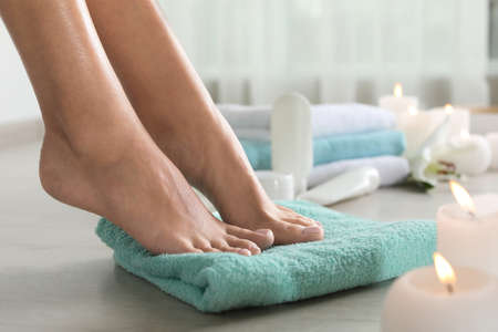 Closeup view of woman with beautiful feet on towel indoors, space for text. Spa treatment