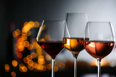 Glasses with different wines against defocused lights, closeup. Space for text