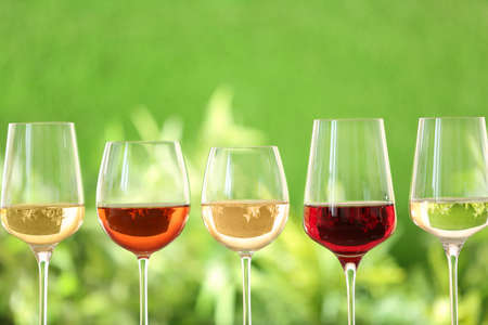 Row of glasses with different wines against blurred background