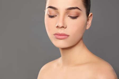 Portret van een jonge vrouw met mooi gezicht en natuurlijke make-up op een achtergrond in kleur, close-up