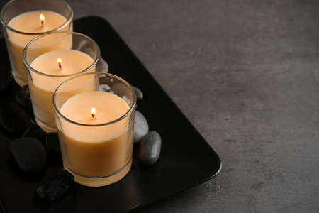 Dark plate with three burning candles and rocks on table, space for text 版權商用圖片