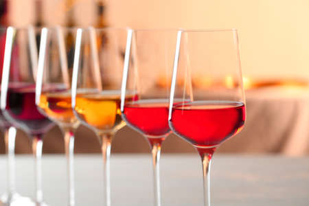 Row of glasses with different wines against blurred background, closeup