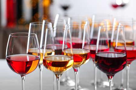 Copas con diferentes vinos sobre fondo borroso, primer plano Foto de archivo