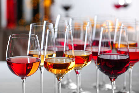 Glazen met verschillende wijnen op onscherpe achtergrond, close-up Stockfoto