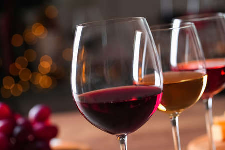 Glasses with different wines against blurred background, closeup