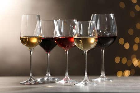 Gläser mit verschiedenen Weinen auf grauem Tisch gegen defokussierte Lichter
