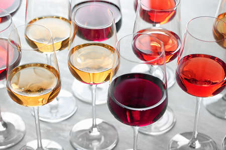 Group of glasses with different wines on light table 写真素材