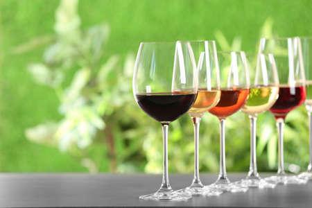 Rij glazen met verschillende wijnen op grijze tafel tegen onscherpe achtergrond. Ruimte voor tekst