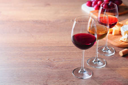 Glasses with different wines and appetizers on wooden table. Space for text