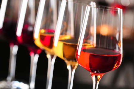 Row of glasses with different wines on blurred background, closeup 写真素材