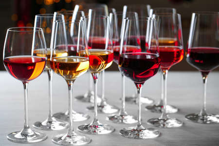 Group of glasses with different wines on table against blurred background 写真素材