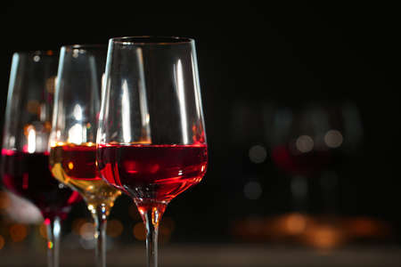 Row of glasses with different wines against blurred background, closeup. Space for text
