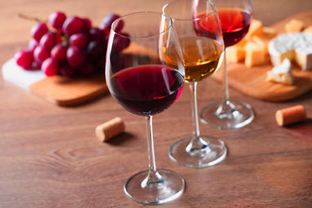 Glasses with different wines and appetizers on wooden table 写真素材