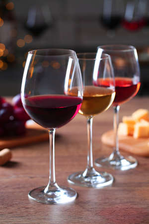 Glasses with different wines and appetizers on wooden table against blurred background