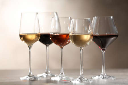 Glasses with different wines on grey table against light background