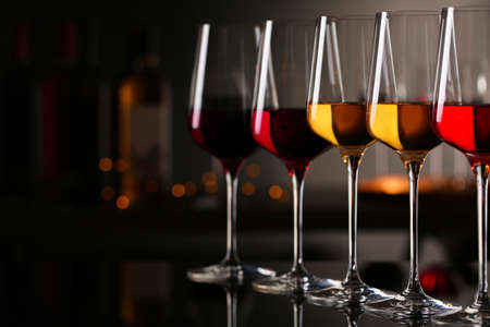 Row of glasses with different wines on bar counter against blurred background. Space for text 写真素材