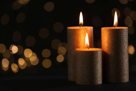 Burning gold candles against blurred lights in darkness. Space for text Archivio Fotografico