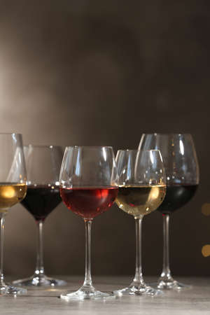 Glasses with different wines on table against dark background. Space for text 写真素材